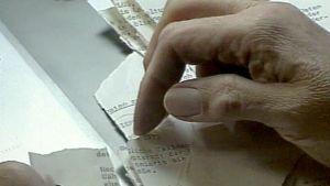Revitteyjä saksankielisiä paperikappaleita käsitellään.