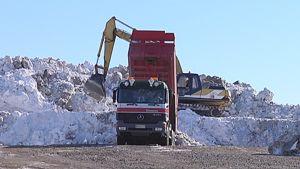 Kuorma-auto kippaa lumilastia lumenkaatopaikalle.