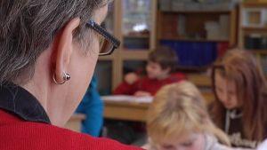 Opettaja valvoo oppilaita luokassa