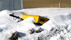 Kuvassa lumihankeen hautautunut peräkärry. Aisa ja kärry etuosaa näkyy hieman lumen keskeltä.