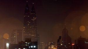 Valaisemattomat pilvenpiirtäjät yötaivasta vasten.