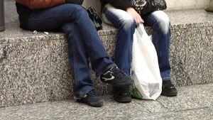 Kaksi tyttöä istuu kauppakeskuksessa.