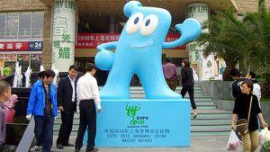 Shanghain maailmannäyttelyn Haibao-hahmo rakennuksen edessä. Ihmisiä ympärillä.