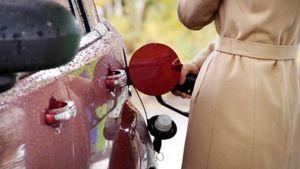Nainen tankkaa autoa huoltoasemalla.