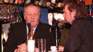 Seppo Kääriäinen ja Johannes Koskinenistuvat pöydässä mikrofonit nenien edessä