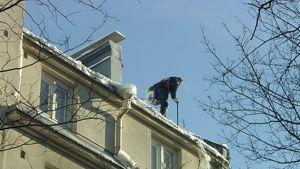 Mies pudottaa lunta kerrostalon katolta aurinkoisessa säässä turvaköyden varassa.