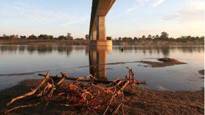 Korkea silta ylittää kuivahkon joen.