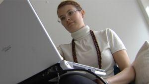 Nuori nainen istuu sohvalla kannettava tietokone polvillaa.