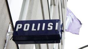 Poliisilaitoksen kyltti ja poliisin lippu.