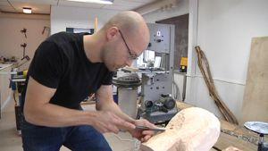 Kuvanveistäjä Riku Riippa työstää puuta taltalla.