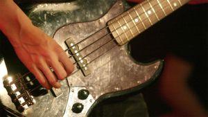 Mies soittaa bassokitaraa.