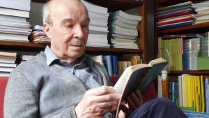 Alpo Räisänen tutkii muistiinpanoja vanhoilta nimenkeruumatkoiltaan.