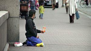 Mies kerjää Helsingin kadulla