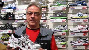 Mies esittelee lenkkikenkiä, taustalla kaupan kenkähylly.
