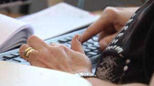 Nainen näpyttelee tietokonetta.