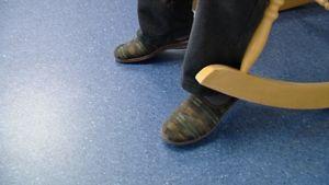 Vanhus kiikkustuolissa, Reino-aamutossut jalassaan.