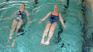 Kuvssa Ritva Björkbacka ja Hanna-Maija Jokela harjoittavat vatsalihaksia vesijuoksuvyön avulla.