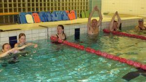 Voimakaksikko-parit lähtevät matkaan uimaopettajan ohjein.