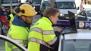 Gasumin työntekijät lukevat mittaustuloksia tietokoneelta räjähdyspaikalla