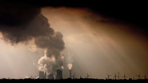 Kivihiilivoimalasta nousee infernaalisen mustansynkeä savupilvi. Ympärillä myös tuulivoimaloita.