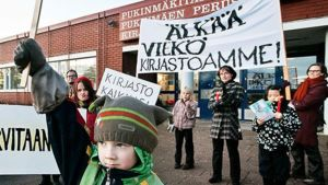 """Joukko naisia ja lapsia osoittaa mieltään Pukinmäen kirjaston edessä. Kulteissä lukee """"Älkää viekä kirjastoamme!"""" ja """"Kirjasto kaikille!""""."""