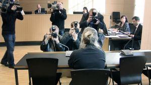 Syytetty hoitaja istuu kuvaajien piirittämänä oikeussalissa.