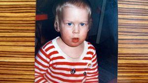 Kuva pienestä Tuomas Kyröstä Marimekon raitapaita päällä.