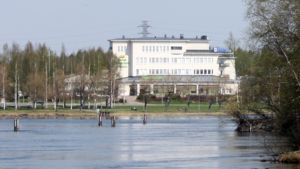 Pohjois-Karjalan osuuskaupan valkea päärakennus Pielisjoen rannalla.