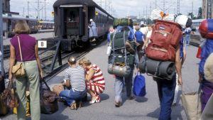 Ihimisiä rautatieasemalla reput selässä.