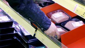 Asiakasnostaa lihapakettia kaupan hyllystä.