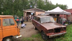 Vanhoja autoja ja tuotantoväkeä hallin pihassa.
