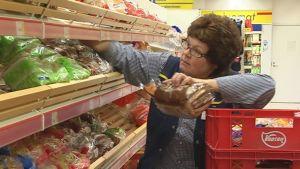 Myyjä täydentää leipähyllyä