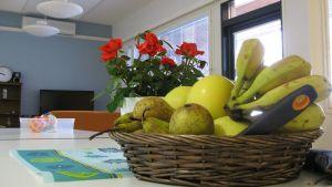 Kuvassa omoenoita, banaaneja ja päärynöitä sisältävä hedelmäkori pöydällä. Etualalla korissa näkyy hedelmäveitsi.