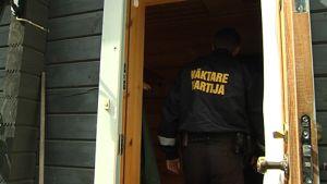 Vartija kävelee puutaloon ulko-ovesta.