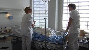 Kaksi sairaanhoitajaa potilaan sängyn luona.
