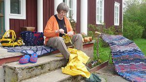 Anna-Liisa Finnilä istuu portailla virkkaamassa. Ympärillä valmiit käsityöt: riippumatto, lapsen keinu, tossut, matto ja kassi.