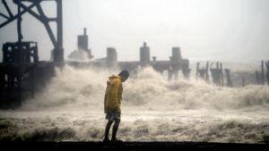 Keltatakkinen mies kävelee myrskyävällä rannalla Guatemalassa.