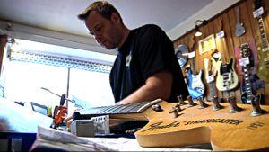 Kitarapajan kitaraspesialisti Jaakko Kiikeri huoltaa kitaraa.