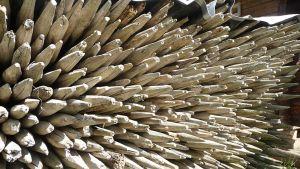 Lähikuvassa pinossa kymmenittäin vanhoja heinäseipäitä