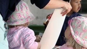 Lastentarhanopettaja ojentaa piirustuspaperia lapselle päiväkodissa.
