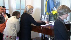 Nainen kirjoittaa Victorian ja Danielin onnittelukirjaan Ruotsin suurlähetyksessä.
