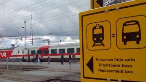 Kuvassa  juna asemalla ja  linja-autoista kertova kyltti.