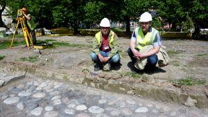 Kaksi miestä arkeologisissa kaivauksissa löydetyn kiveyksen edessä, taustalla mittaaja