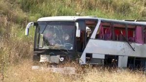 Räjäytetty linja-auto keskellä heinikkoa