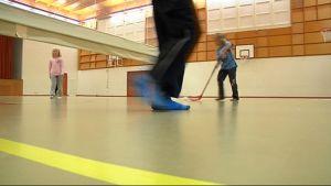 Koululaisia pelaamassa sählyä liikuntasalissa.