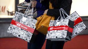 Naisten käsissä H&M -vaateliikkeen ostoskasseja.