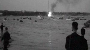 Ihmisiä katsomassa juhannuskokkoa, mustavalkoinen kuva vanhasta suomalaisesta elokuvasta.