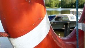 Pelastusrenkaan reiästä näkyy vene laiturissa ja merta.