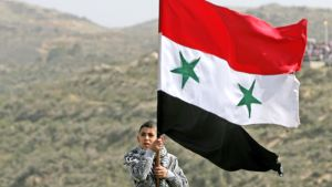 Nuori poika heiluttaa Syyrian lippua Golanin kukkuloilla.