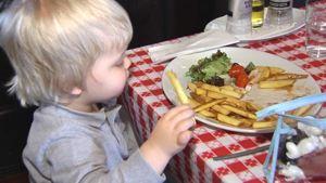 Pikkupoika syö ranskalaisia ravintolassa